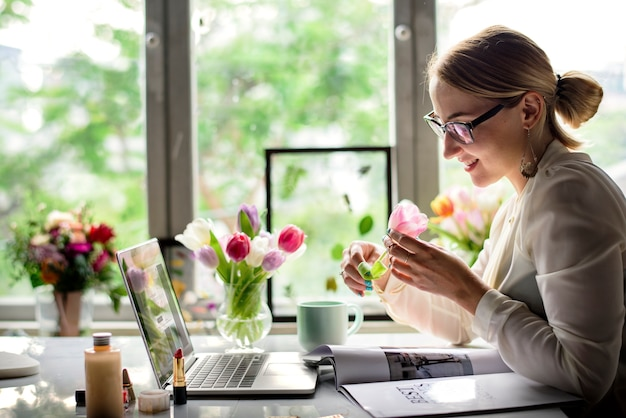 Vrouw die een bloem in het bureau ruikt