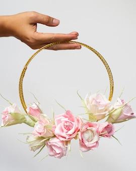 Vrouw die een bloemenframe op witte achtergrond houdt