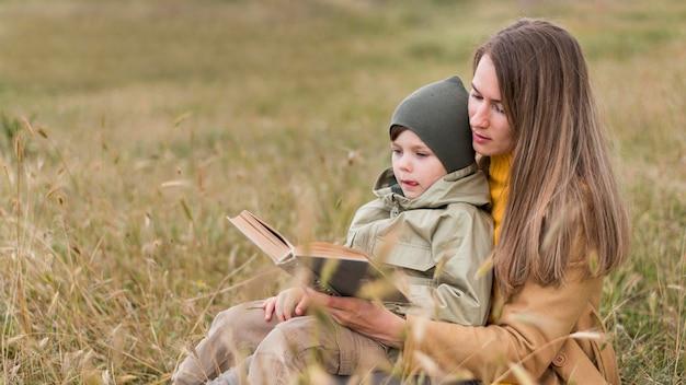 Vrouw die een boek buiten leest aan zijn zoon
