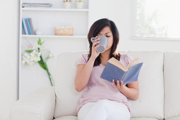 Vrouw die een boek en het drinken houdt