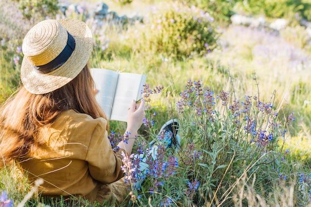 Vrouw die een boek in aard leest die door vegetatie en bloemen wordt omringd