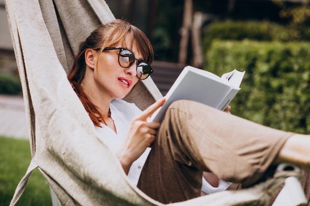 Vrouw die een boek in de tuin door het huis leest