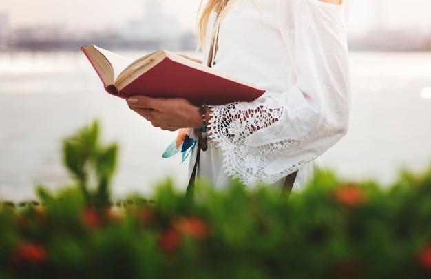 Vrouw die een boek leest door het water