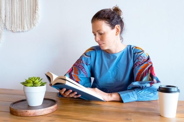 Vrouw die een boek leest met een kopje koffie, zittend in een café.