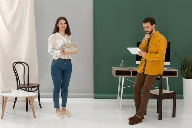 Vrouw die een boek leest terwijl de man tablet gebruikt