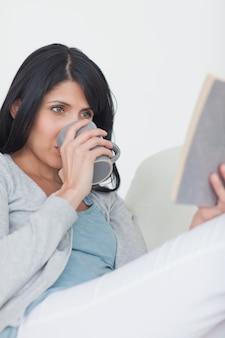 Vrouw die een boek leest terwijl het drinken van a van een mok