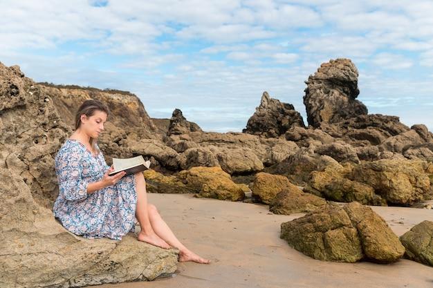 Vrouw die een boek leest, zittend op een rots op het strand