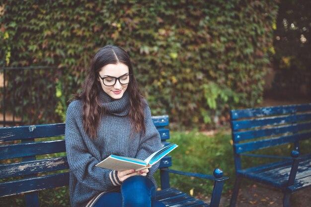 Vrouw die een boek op de bank in een park leest