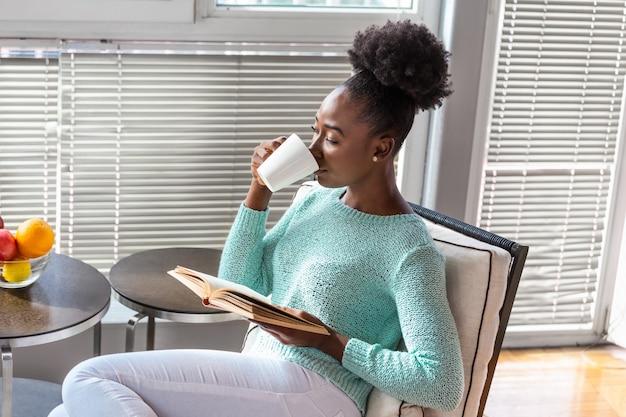 Vrouw die een boek op een stoel leest