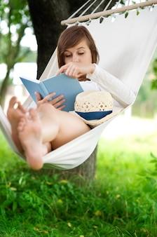 Vrouw die een boek op hangmat leest