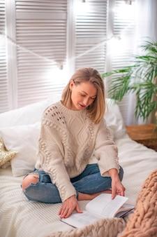 Vrouw die een boek op het bed leest