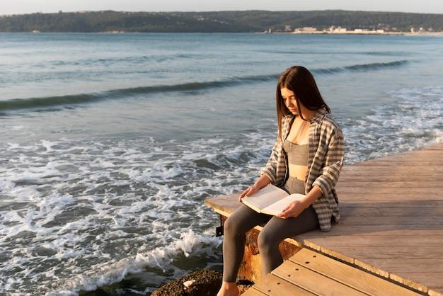 Vrouw die een boek op het strand leest