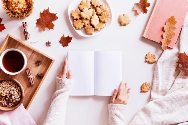 Vrouw die een boek over een lijst met koffiekop, koekjes en herfstbladeren leest. bovenaanzicht