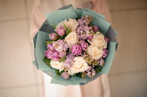 Vrouw die een boeket van tedere heldere violette en perzik kleurenbloemen houdt