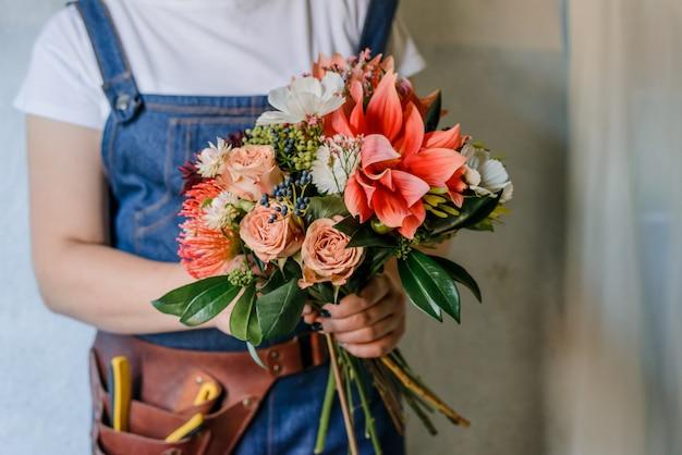 Vrouw die een boeket van verse tuinpioenen maakt. een lenteboeket maken met rode en oprange bloemen. heuptasje voor bloemist en decorateur