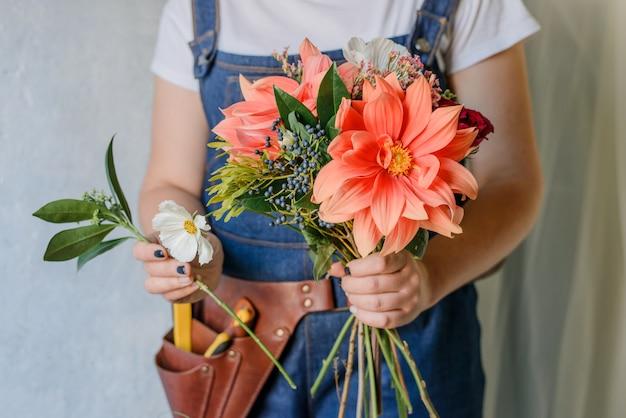 Vrouw die een boeket van verse tuinpioenen maakt. een lenteboeket maken met rode en oprange bloemen.