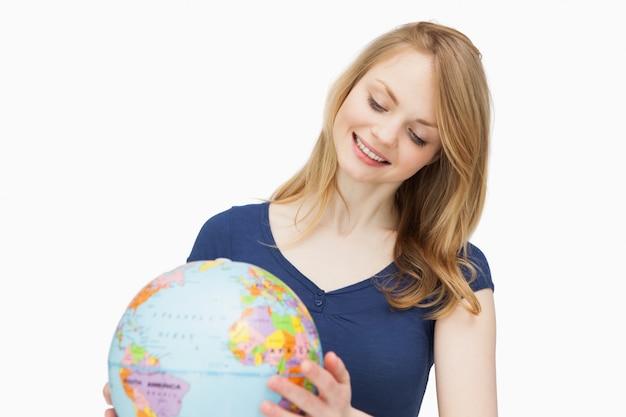 Vrouw die een bol houdt terwijl het glimlachen