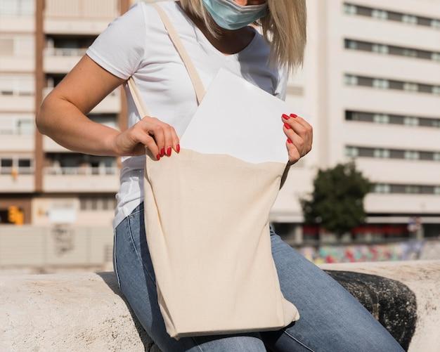 Vrouw die een boodschappentas draagt en een masker draagt