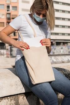 Vrouw die een boodschappentas draagt en een medisch masker draagt