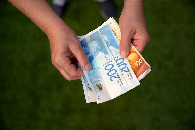 Vrouw die een bos van israëlische nieuwe shekel-bankbiljetten in haar handen houdt