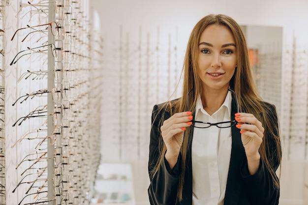 Vrouw die een bril kiest bij optisch lab