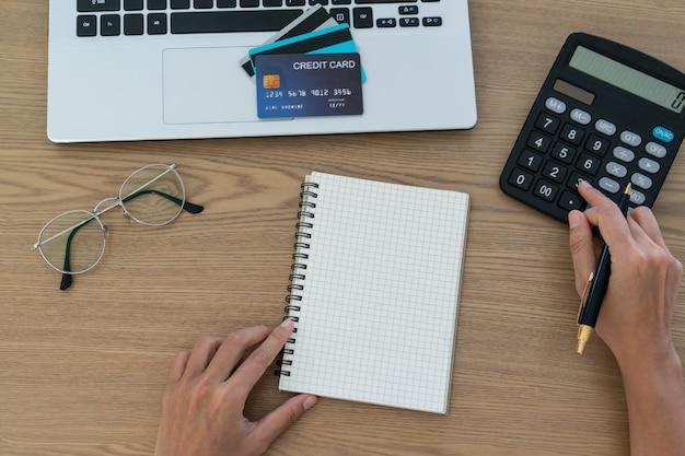 Vrouw die een calculator, een rekening en een besparingsconcept gebruiken.