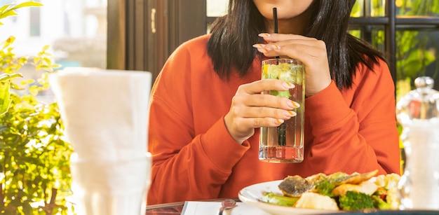 Vrouw die een cocktail drinkt in het restaurant