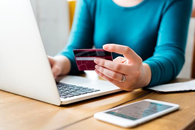 Vrouw die een creditcard houdt en aan haar laptop werkt