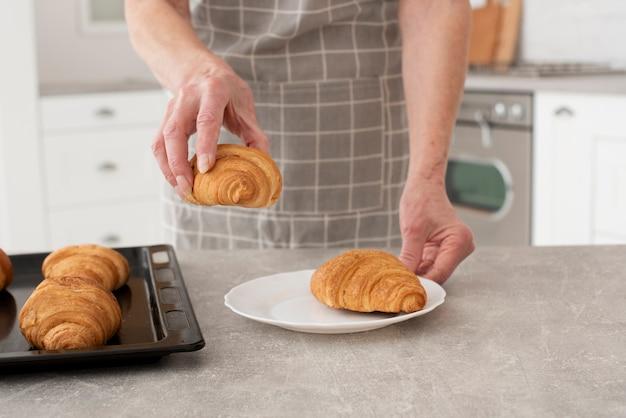Vrouw die een croissant in de keuken houdt Gratis Foto