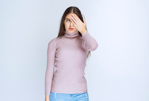 Vrouw die een deel van haar gezicht sluit en over de vingers kijkt.