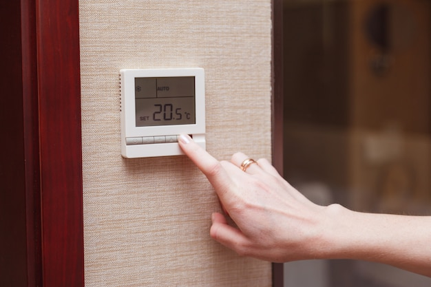 Vrouw die een digitale thermostaat schakelt