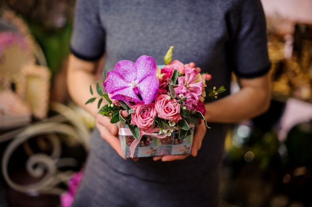 Vrouw die een doos met roze rozen en hyacinten houdt