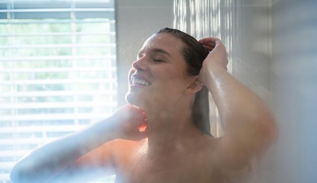 Vrouw die een douche in badkamers neemt