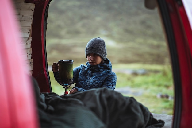 Vrouw die een draagbaar kampeerfornuis gebruikt om water te koken