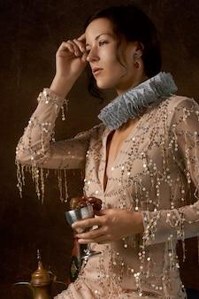 Vrouw die een elizabethaanse kraag draagt en een miskelk draagt die met druiven wordt gevuld