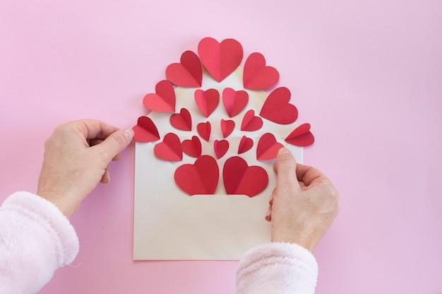 Vrouw die een envelop van harten voorbereidt om als gelukwensen op de dag van valentine te verzenden