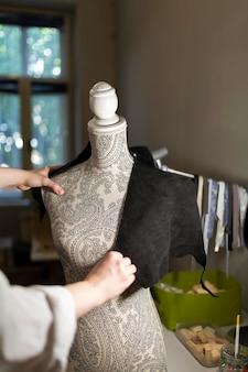 Vrouw die een etalagepop gebruikt om kleding te maken