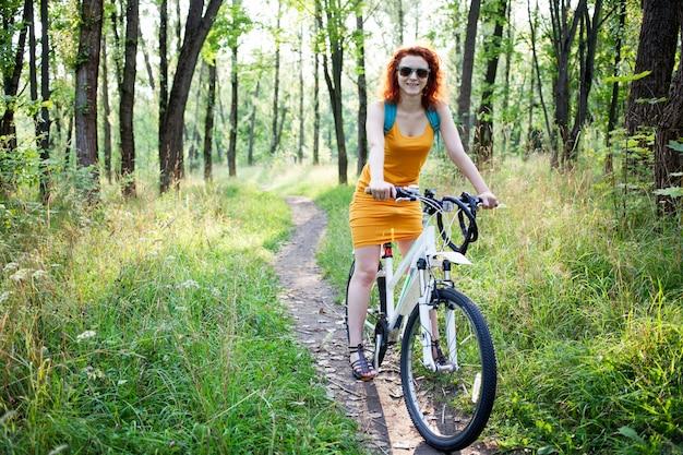 Vrouw die een fiets in groen bos berijdt