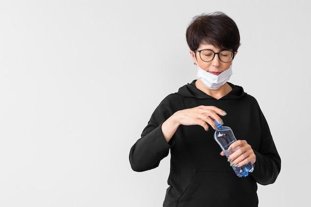 Vrouw die een fles water met exemplaarruimte opent