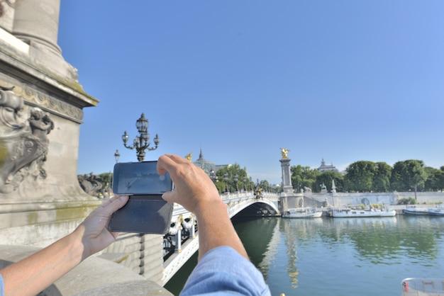 Vrouw die een foto met een smartphone in parijs neemt
