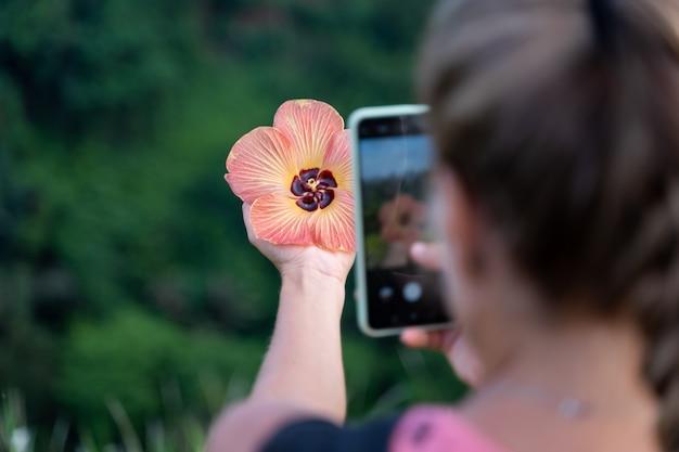 Vrouw die een foto met haar mobiele telefoon neemt van een bloem die ze in haar hand houdt