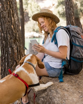 Vrouw die een foto van haar hond in het bos neemt