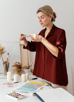 Vrouw die een foto van haar kunst met haar telefoon neemt