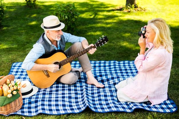Vrouw die een foto van zijn man met een gitaar neemt