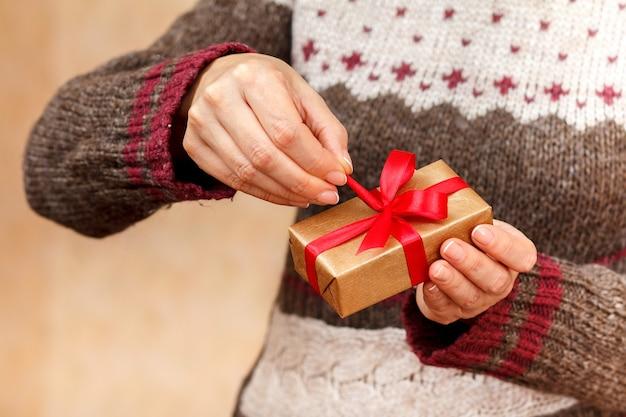 Vrouw die een geschenkdoos met rood lint in haar handen houdt en probeert deze te openen. ondiepe scherptediepte, selectieve focus op de doos. concept van het geven van een cadeau op vakantie of verjaardag.
