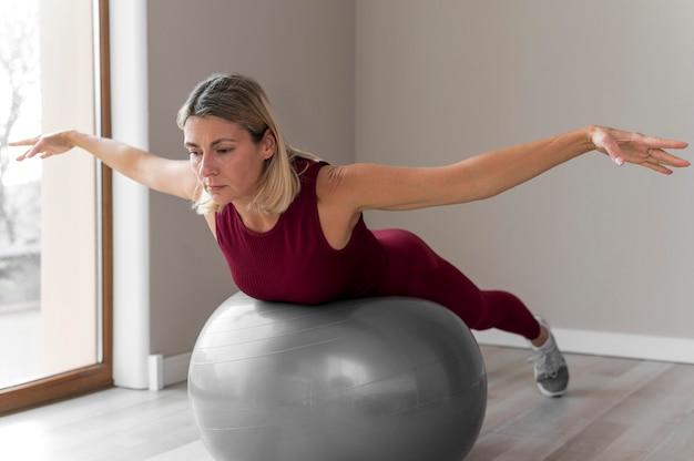 Vrouw die een geschiktheidsbal gebruikt voor haar training