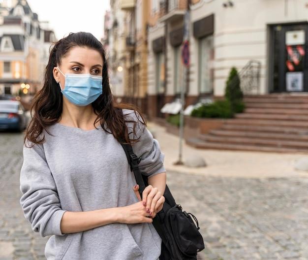 Vrouw die een gezichtsmasker buiten met exemplaarruimte draagt