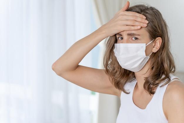 Vrouw die een gezichtsmasker draagt om zich ziek te voelen, hoofdpijn en hoest vanwege coronavirus covid-19 in quarantainekamer