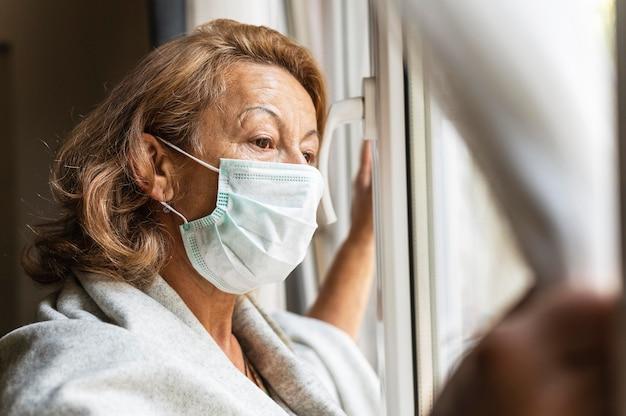Vrouw die een gezichtsmasker draagt terwijl ze uit het raam kijkt