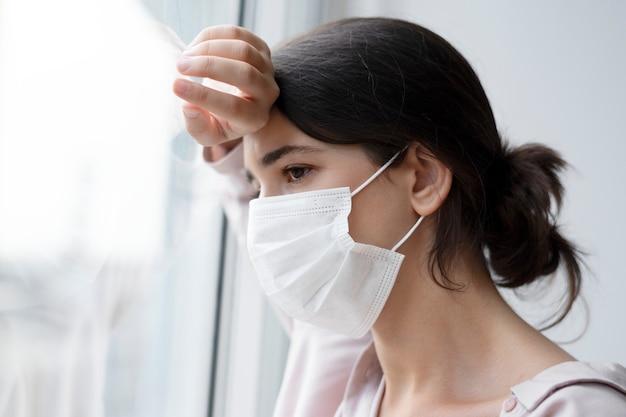 Vrouw die een gezichtsmasker draagt tijdens thuis